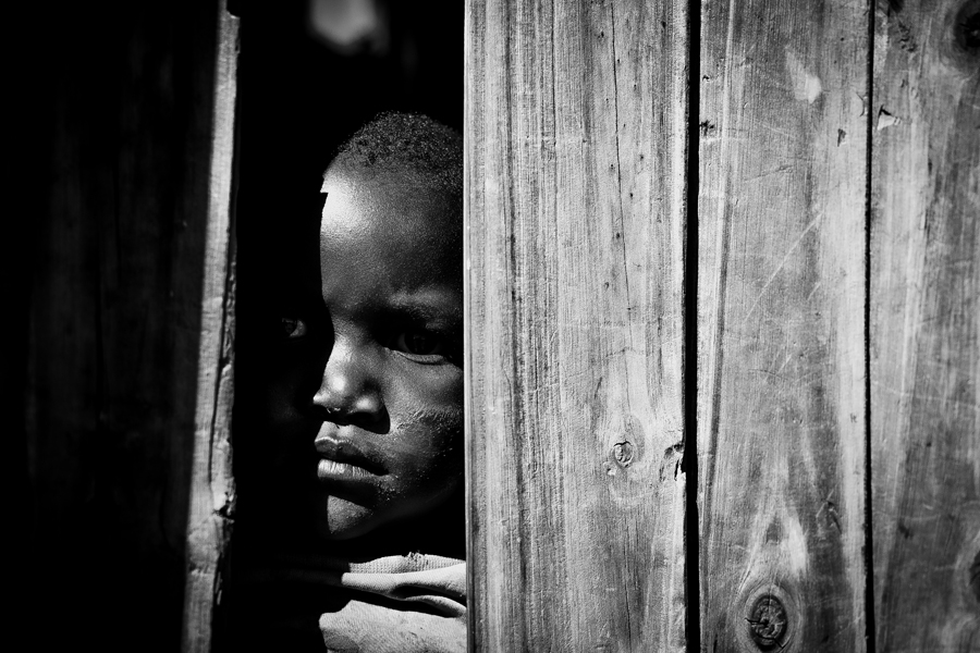 Child peering from behind wooden door, 2016