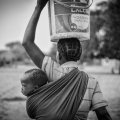 Woman carrying child on back, bucket on head, 2016